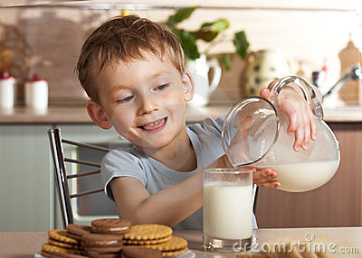 Little boy pours milk from jug