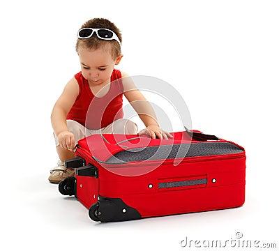 Little boy preparing for trip, zipping suitcase