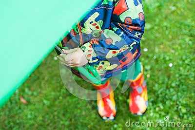 Little boy in rain clothes and boots hiding under green umbrella