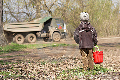 The little boy with a red children s bucket
