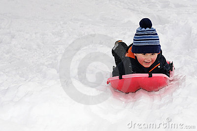 Little boy on red sled