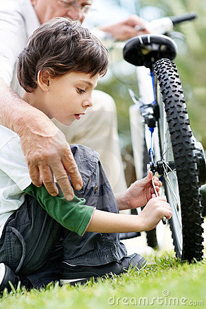 Little boy repairing a cycle tyre with grandfather