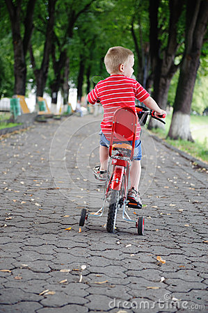 Little boy riding a bike in park