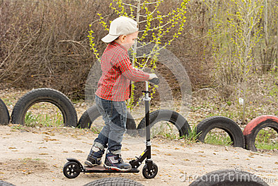 Little boy riding his scooter on a dirt lane