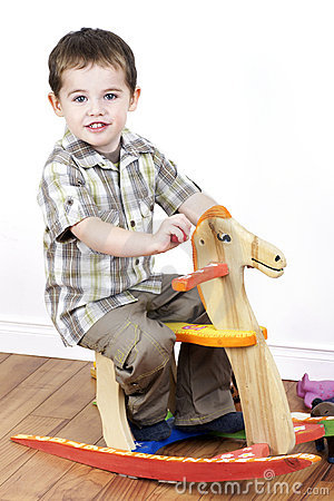 Little boy riding a rocking horse