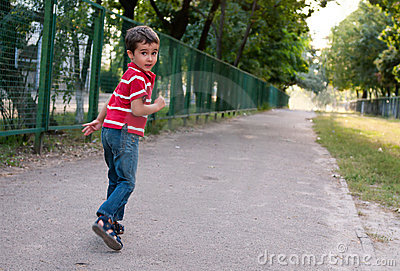 Little boy run by the fence