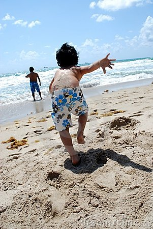 A little boy running into the ocean