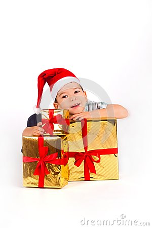 Little boy in Santa hat with a bunch of gifts