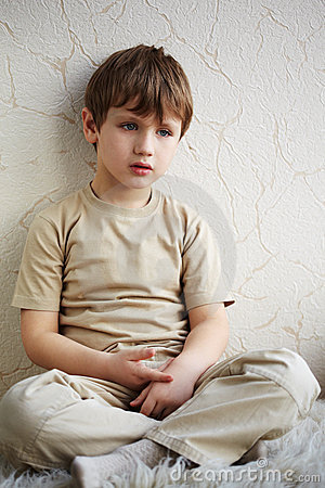 Little boy sits alone on fleecy white rug