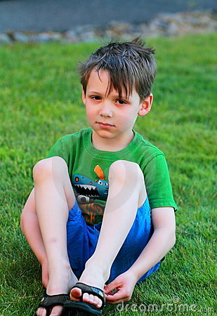 Little boy sits in the grass.