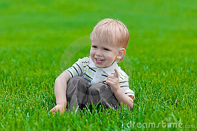 Little boy sitting and dreaming in green grass