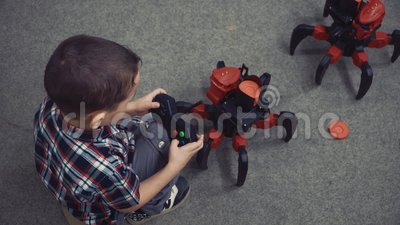 Little boy sitting on the floor with the remote control participates in the battle of the robots.  stock video