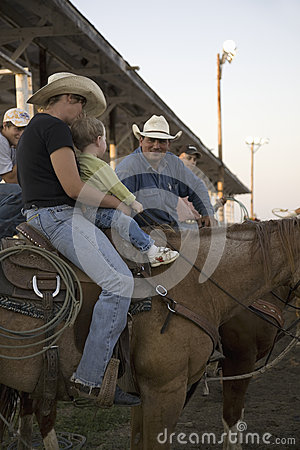 Little boy sitting on horse with cowboy at PRCA Rodeo Editorial Image