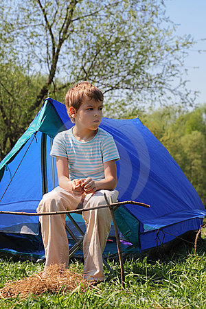 Little boy sitting near blue tent on nature