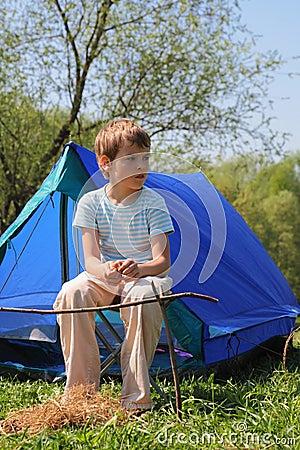 Little boy sitting near blue tent on nature