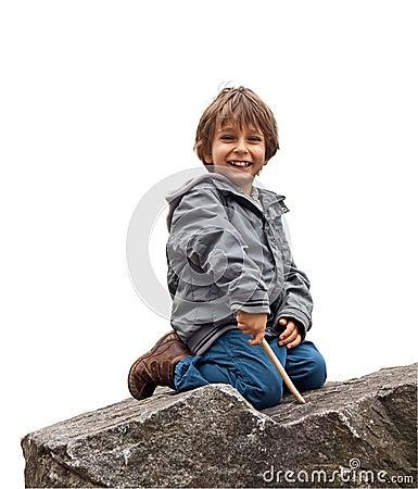 A little boy sitting on a rock.