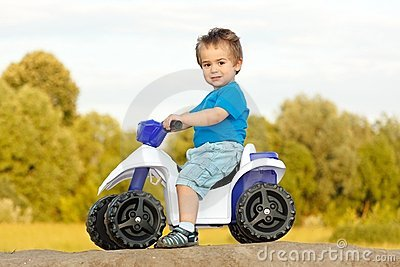 Little boy sitting on toy quad