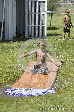 Little boy sliding on a water slide Editorial Image