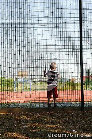 Little boy standing near grid fence