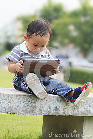 Little boy staring at a tablet