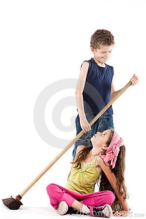 Little boy sweeping angry little girl