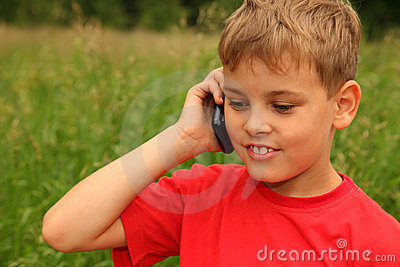 Little boy talking on cell phone outdoors