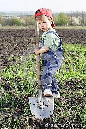Little boy to dig on field