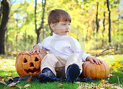Little boy with two helloween pumpkins