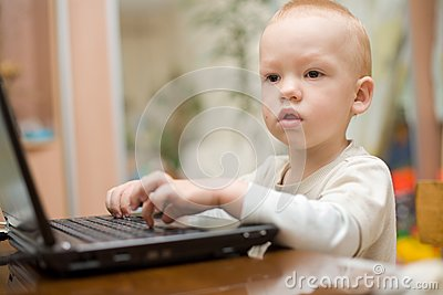 Little boy typing text on laptop at home