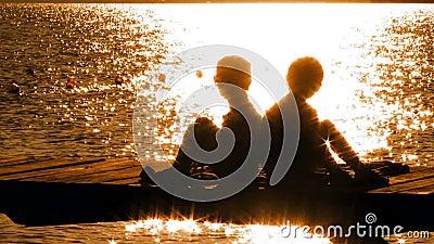 Little Boy und Mädchen, die auf Brücke bei Sonnenuntergang sitzen stock video footage