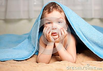 Little boy under a blue blanket