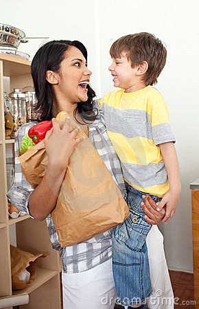 Little boy unpacking grocery bag with his mother