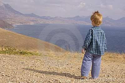 Little boy walk in summer mountain