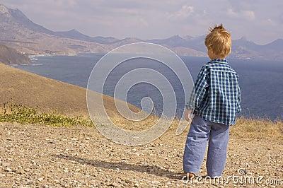 Little boy walk in summer mountain