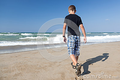 A little boy walking alone on the beach 1
