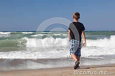 A little boy walking alone on the beach 2