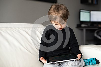 Little boy watching a movie on tablet