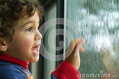 Little boy watching the rain
