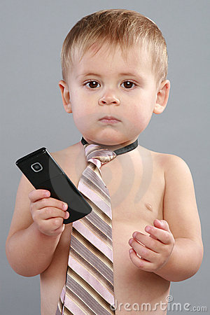 Little boy wearing a tie and a cellphone