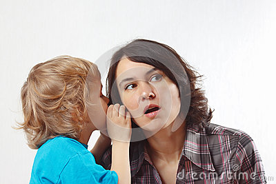 Little boy whispers to his mother something into her ear