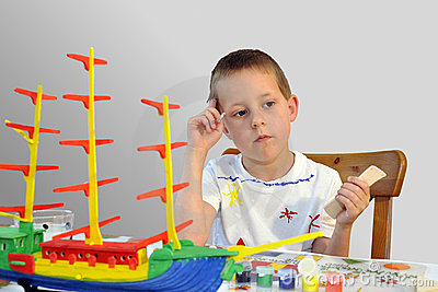 Little boy - woodcraft ship painting, thinking