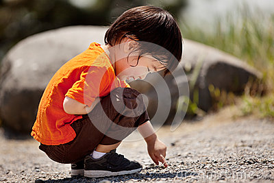 Little boy writing on the ground