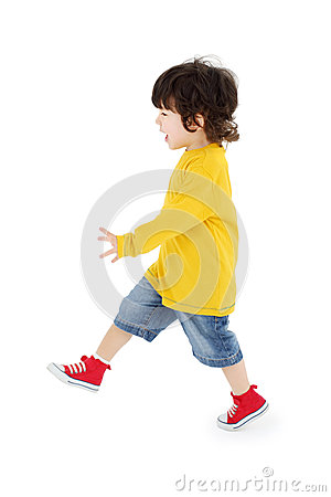 Little boy in yellow shirt walks isolated