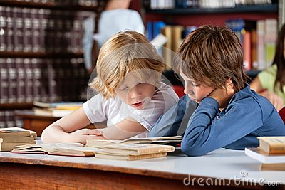 Little Boys Reading Book Together In Library