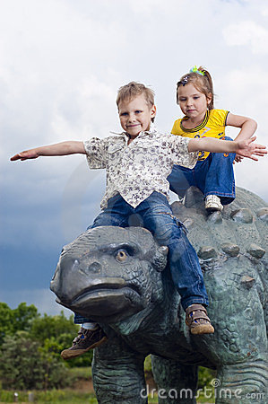 Little brave children on a dinosaur in a park