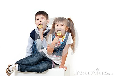 Little brother and sister eating tasty candies