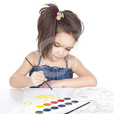 Little brunette girl drawing at the desk