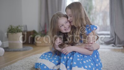 Little Caucasian girl hugging her adorable twin sister and smiling. Two positive identical kids expressing their love at. Home. Unity, lifestyle, joy, happiness stock footage