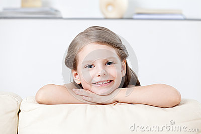 Little child leans to the white leather sofa