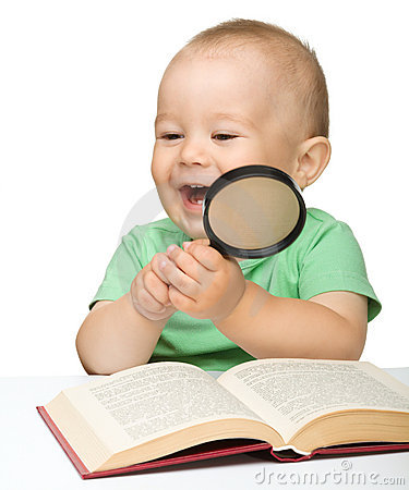 Little child play with book and magnifier